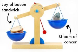 Scales showing bacon sandwich outweighing cancer