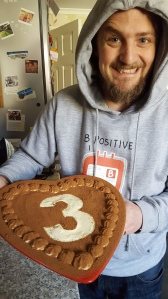 George showing off a heart-shaped cake with 3 on the top